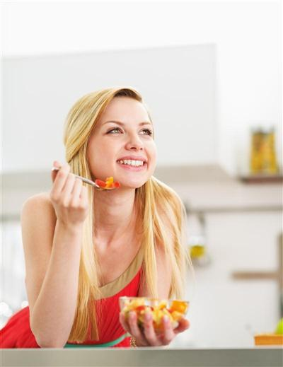 Happy young woman eating fresh fruits salad in kitchen