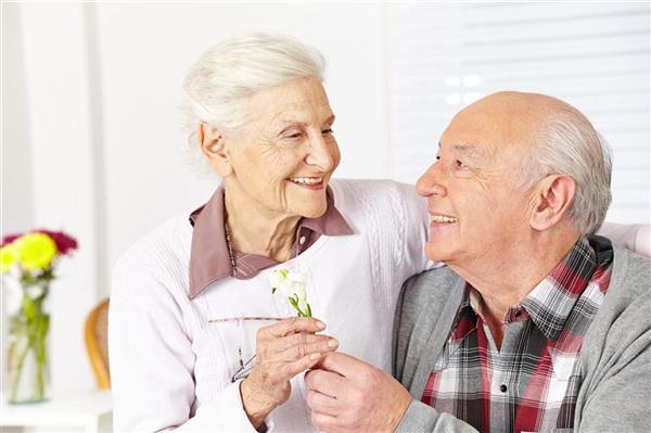 Happy senior citizen giving a freesia flower to smiling woman
