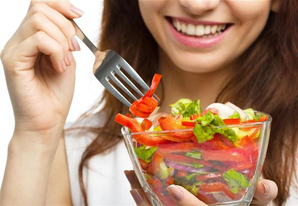 Young attractive woman eats vegetable salad using fork, isolated over white