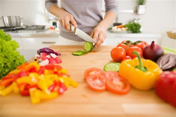 Close up on young woman slicing vegetables